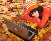 Young woman in autumn orange leaves with laptop. Fall sale. Outdoor.