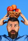 Farmer With Concentrated Face Holds Red Apples On Head. poster