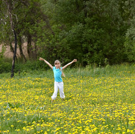 stock photo of hands up  - Little girl on meadow outdoor  with hand up - JPG