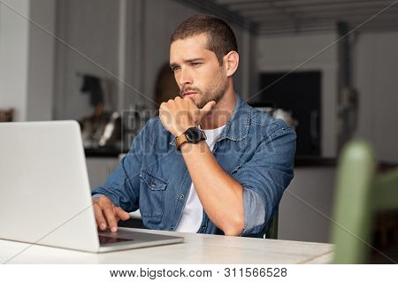 poster of Serious young man working on laptop at home. Focused entrepreneur working on computer sitting at tab