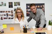 Portrait of Caucasian male and female graphic designers smiling at desk. This is a casual creative s poster