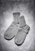 Hand-knitted grey wool socks on grey background