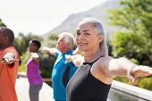 Portrait of happy senior woman practicing yoga outdoor with fitness class. Beautiful mature woman st poster