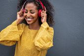 African girl listening to music with her wireless headphones while leaning against grey wall. Happy  poster
