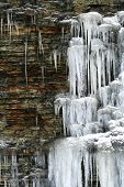 pic of shale  - colorful shale cliff rock layers lined with snowy  ice cascades - JPG