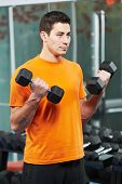 Smiling bodybuilder athlete man at biceps brachii muscles exercises with training dumbbells in fitne