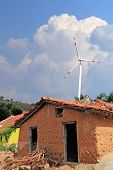stock photo of mud-hut  - Old mud house in rural india with wind mill in the backdrop - JPG