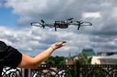 Drone Landing On Hand. Drone And Photographer Man Hands.drone Copter Flying With Digital Camera poster