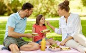 family, leisure and people concept - happy mother, father and daughter having picnic at summer park poster