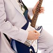man in white suit playing guitar