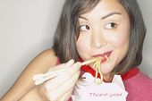 Asian woman eating Chinese takeout with chopsticks