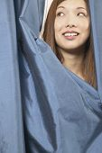 Asian woman peeking out from curtain