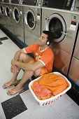 picture of laundromat  - Man sitting on floor listening to music in laundromat - JPG