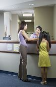 Rear view of mother and daughter at reception desk of clinic