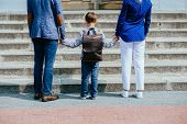 Parents And Pupil Of Primary School Stands Hand In Hand Before Stairs. Father, Mother And Son With B poster