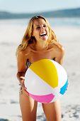 jovem saudável rir com beachball enquanto na praia no verão