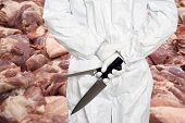 Butcher standing in front of a large stack of raw meat (pork chops), with his back to the camera, ho