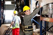 Portrait of happy young foreman lifting cardboard box with coworker pushing handtruck at warehouse