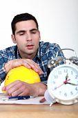 Builder being woken up by alarm clock