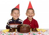 picture of birthday party  - Two brothers aged 5 and 6 years wearing funny party hats and ready to enjoy a birthday cake isolated over white background - JPG