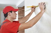 Young professional handyman worker in uniform measuring length of the wall