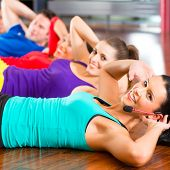 Fitness group with instructor in gym doing stomach crunches for sport