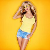 Young Woman In Yellow Tanktop And Eye Glasses Against Yellow Background