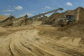 stock photo of earth-mover  - industrial location where sand is extracted and place to the sun for evaporation and then selected - JPG