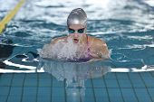 Young Girl Swims Breaststroke In The Swimming Pool