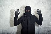 stock photo of caught  - Catch the burglar concept thief with balaclava caught in front of the grunge concrete wall - JPG