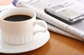 Coffee, Cellphone And Newspaper On Work Table