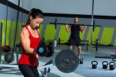 girl dumbbell and man weight lifting bar workout at gym