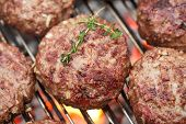 food meat - raw burgers on bbq  barbecue grill with fire. Shallow dof.