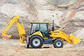 stock photo of backhoe  - Wheel loader Excavator with backhoe loading sand at eathmoving works in construction site - JPG
