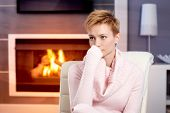 Attractive young woman sitting by fireplace at home in pink pullover, thinking.
