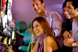 stock photo of slot-machine  - happy friends at the casino on the slot machines - JPG