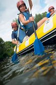 stock photo of raft  - A group of friends in an inflatable raft moving down a river - JPG