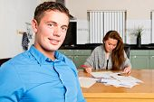 Young Man, sitting at the kitchen table, as he just finished getting her personal finances in order,