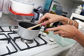 Cropped image of senior woman cooking at kitchen counter