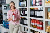 Portrait of beautiful young woman holding bottle of alcohol at supermarket