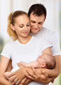 Happy Young Family Of Mother, Father And Newborn Baby In Their Arms