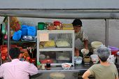 PENANG, MALAYSIA - APRIL 2012 : A man making noodles at noodle stall on Lebuh Campbell street in Pen