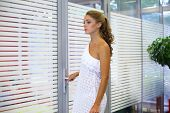A beautiful girl stands in front of a glass door