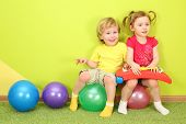Boy and girl with pigtails sitting on the colorful balls, girl holding metallophone on knees