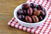 ripe black kalamata olives in a white bowl