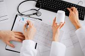 healthcare, hospital and medical concept - two doctors prescribing medication