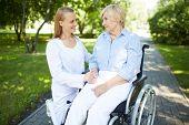 Pretty nurse talking to senior patient in a wheelchair in park