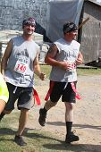 MUSKOGEE, OK - Sept. 14: Runners wearing red life flags overcome obstacles and avoid zombies during