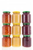 Stacked glass pots with canned vegetables isolated over white background