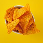 a bowl with tortilla chips on a yellow background
